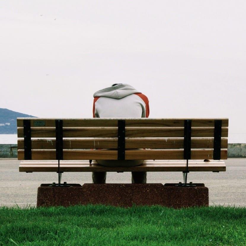 chico con distimina triste en un banco sentado