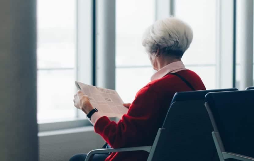 mujer mayor recordando con periódico de otra época