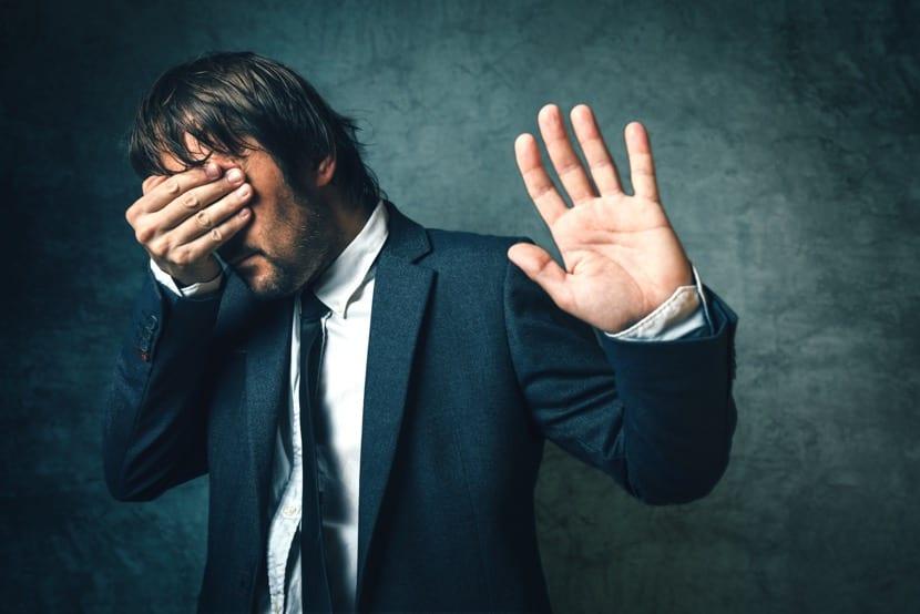 hombre que se tapa la cara porque siente vergüenza ajena